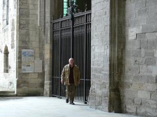 Un homme marche devant la grille fermée d'une église ou d'un monastère