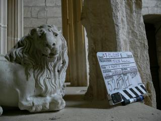 Un clap est posé à côté d'une statue de lion