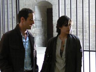 Un homme et une femme sont devant la grille (à l'intérieur) entourant un monastère