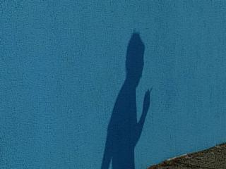 Ombre d'une femme fumant une cigarette, sur un mur bleu