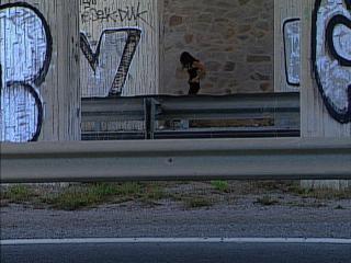 Femme devant un mur de pierre, derrière des rambardes métalliques