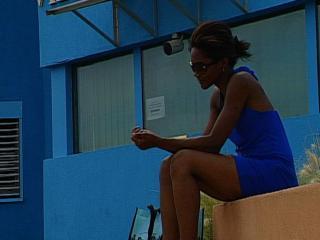 Femme assise sur un muret, les yeux baissés, devant un bâtiment bleu équipé de caméra de surveillance