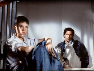 Un jeune homme et un homme sont assis au sol, ils regardent dans la mpeme direction