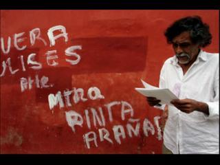 Devant un mur rouge recouvert d'inscriptions blanches, un homme barbu lit une série de feuillets qu'il tient dans la main