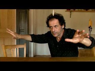 Pascal Comelade, assis à une table, fait de grands gestes avec les bras
