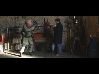 Dans un garage, un père vise son fils avec un fusil de chasse