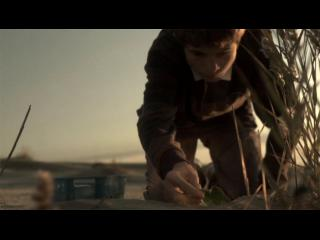 Un jeune homme est penché sur le sable, il y inscrit quelque chose