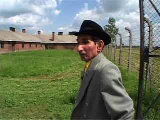 Un rom, coiffé d'un chapeau noir, marche dans une étendue d'herbe, entourée de clôtures