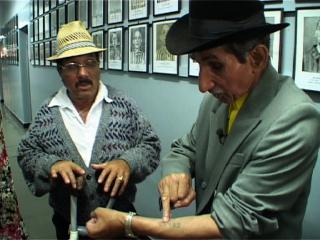 Un homme rom, coiffé d'un chapeau noir, parle avec un homme lui aussi coiffé d'un chapeau, dans une salle aux murs couverts de photos en noir et blanc encadrées
