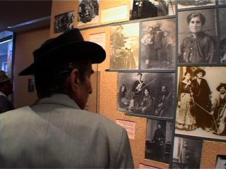 Un homme rom, coiffé d'un chapeau noir, regarde des photos en noir et blanc exposées sur un mur