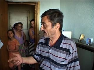 Un homme rom parle, derrière lui, dans entrebâilleur de la porte, quatre femmes et jeunes filles