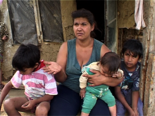 Mère rom qui porte ses trois enfants dans les bras tout en faisant la manche