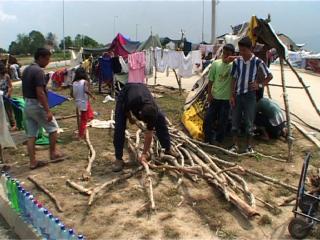 Dans un camp rom, des jeunes hommes construisent un étendoir à linge