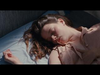 Jeune fille assoupie sur un lit au drap blanc