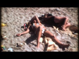 Couple en maillots de bain allongé sur le sable à la plage