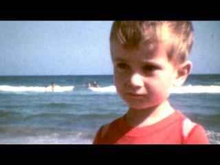 Petit garçon avec un t-shirt rouge, devant la mer