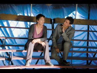 Couple assis dans les gradins d'un cirque, sous un chapiteau bleu ciel
