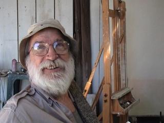 Piet Moget souriant, dans son atelier, près d'un chevalet