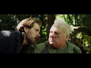 Un homme parle avec son père, dans la nature. Ils se regardent avec une sorte de dépit