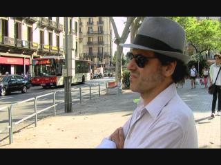 Pascal Comelade, assis sur un banc en ville, de profil