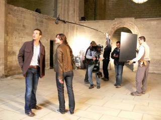Scène de tournage : les deux acteurs sont au premier plan, derrière eux l'équipe technique en train de tourner