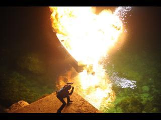 Homme projeté derrière un tas de sable lors d'une explosion