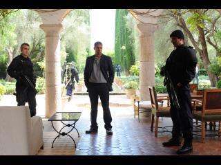 Dans une grande villa ornée de colonnes romaines, un homme et deux autres armés et habillés de noir