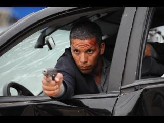 Un homme tirant des coups de revolver depuis la fenêtre d'une voiture