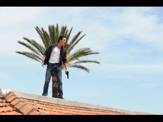 Homme armé, sur le toit d'une maison, derrière lui, un palmier