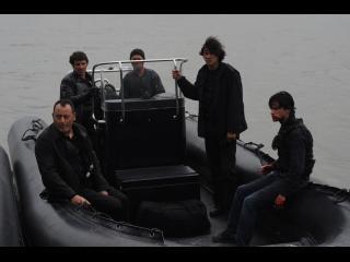 Cinq hommes armés et habillés de noir, en mer, sur un bateau à moteur