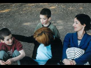 Deux femmes assises dans l'herbe, entourées par deux petits garçons