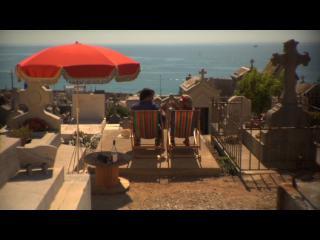 Sur une terrasse qui a vue sur la mer, deux personnes se prélassent dans des chaises longues