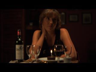Une femme, seule, attend à une table de restaurant, devant elle, un verre de vin rouge et un petit gâteau au chocolat sur lequel est posée une bougie