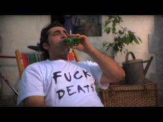"""Un homme est allongé dans une chaise longue et boit une bière, il porte un t-shirt sur lequel est inscrit """"Fuck Deats"""""""