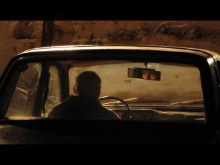 Un homme est assis dans une voiture, seul, il regarde au loin
