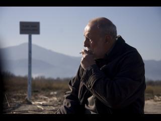 Un homme d'environ quatre-vingts ans fume une cigarette au bord d'une route
