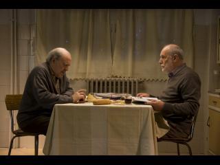 Deux hommes d'environ quatre-vingts ans sont assis face à face à une table et mangent en parlant