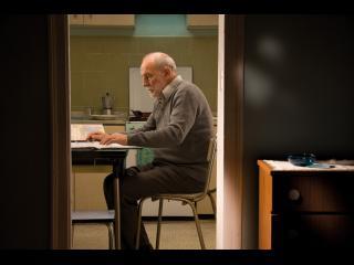 On voit à travers le cadre d'une porte un homme d'environ quatre-vingts ans assis à une table, en train de lire un journal