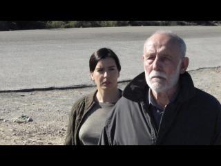 Sur la plage : un homme d'une soixantaine d'années marche, derrière lui, une jeune femme marche et essaye de lui parler