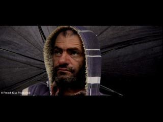 Portrait d'un homme brun, barbu, sous un parapluie noir