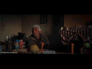 Un homme est assis dans une salle à manger aux murs abimés