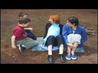 Deux femmes, dont l'une est enceinte, et deux enfants assis par terre sur une couverture