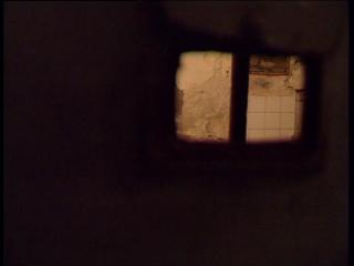 Par un fenestron grillagé, on aperçoit l'intérieur d'une cellule de prison