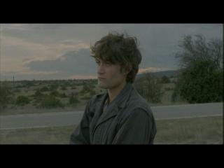 Un jeune homme est debout, au bord d'une route perdue au milieu de nulle part