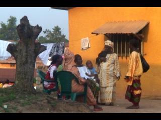 Une groupe de femmes et d'enfants d'origine africaine discutent devant une maison jaune