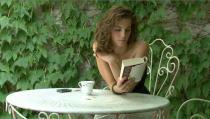 Une jeune femme aux épaules dénudées lit un livre assise à une table de jardin, derrière elle, un mur couvert de lierre