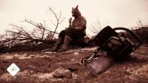 Un homme kangourou est assis sur une pierre, dans la garrigue, devant lui, sur le sol, une tronçonneuse