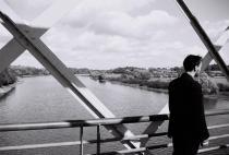 Photo en noir et blanc d'un homme en costume noir, de dos, sur un pont au-dessus d'une étendue d'eau