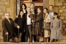 Photo de famille devant la porte d'une maison en pierre
