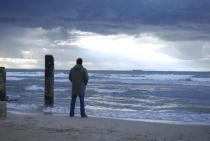 Un homme de dos debout face à la mer